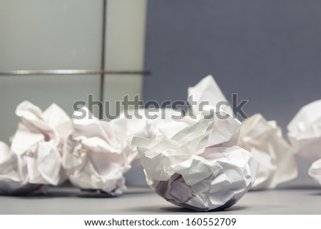 Crumble paper balls on gray ground with part of bin - stock photo