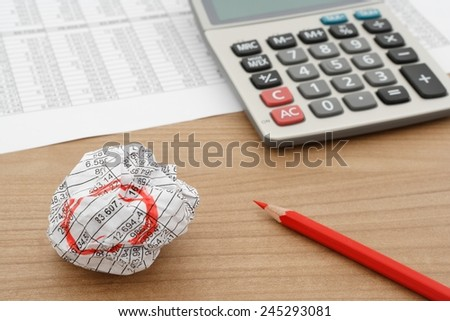 crumbled document on wooden table with calculator and red pencil, selective focus