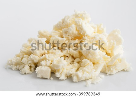 Crumbled white feta cheese isolated on white surface.