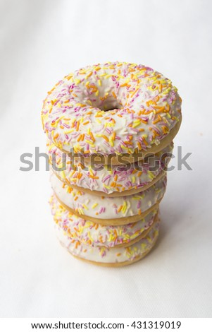 Crumpets are stacked in a column. Donuts for tea. Tasty food cakes. Delicious classic cakes: fried doughnuts glazed with caramel. Nutritious dish that promotes obesity. - stock photo