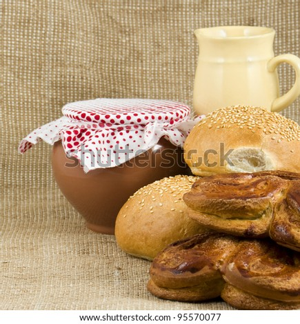 crumpets with sesame lie on each other on a background a pot and milkman on rough material - stock photo