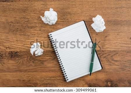crumple white paper and pen with notebook on the desk - stock photo