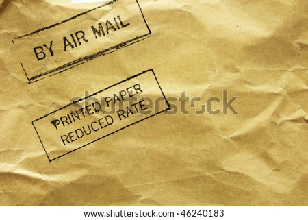 "Crumpled brown letter envelope with ""Air Mail"" and ""Printed paper reduced rate"" stamps."