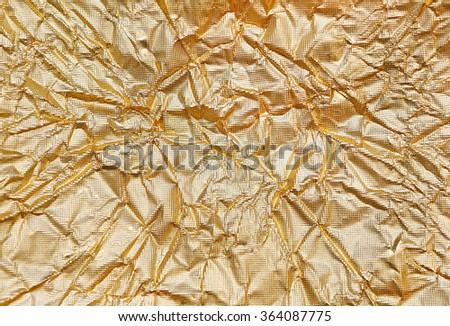 Crumpled golden Aluminum Foil Background Texture - stock photo