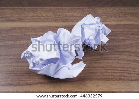 Crumpled paper balls isolated on wooden background. Copy space