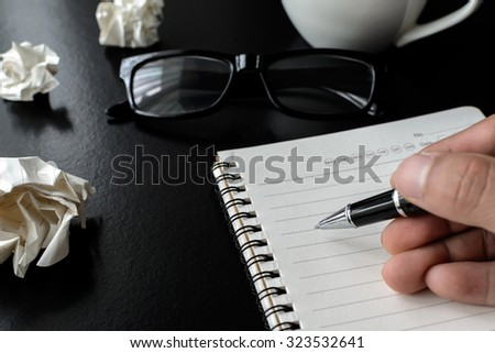 Crumpled paper balls with eye glasses and hand writing - stock photo