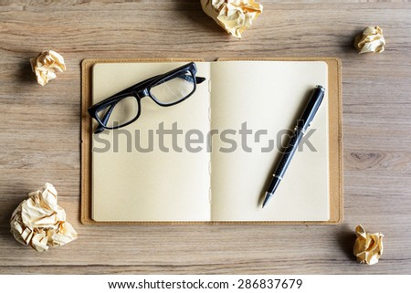 Crumpled paper balls with eye glasses and notebook on wood desk, creative writing concept - stock photo
