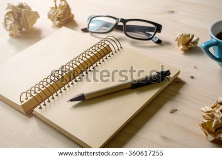 Crumpled paper balls with eye glasses, pen and notebook with soft light - stock photo