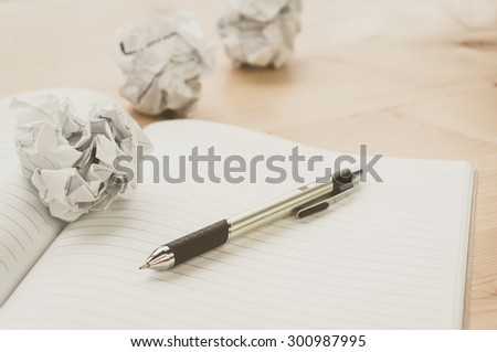 Crumpled paper balls with pen and notebook on wood desk.vintage effect style picture - stock photo