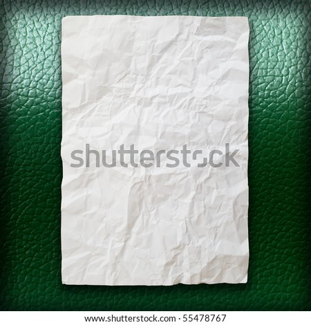 Crumpled paper on green leatherette background - stock photo
