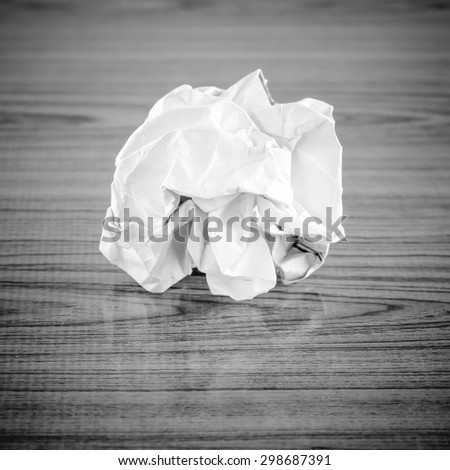 crumpled paper on wood background black and white color tone style