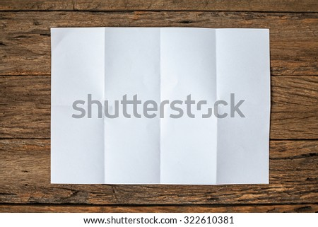 Crumpled paper on wooden background - stock photo