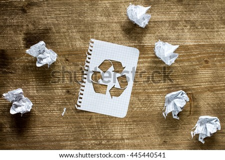 Crumpled paper pieces and paper with recycle sign  - stock photo