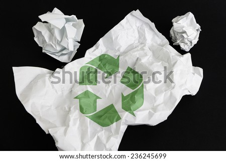 Crumpled paper sheet with Recycling Symbol isolated on black - stock photo