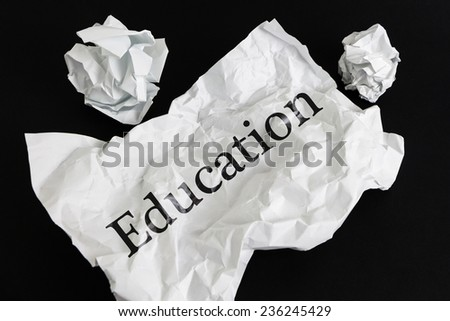 Crumpled paper sheet with word Education isolated on black - stock photo
