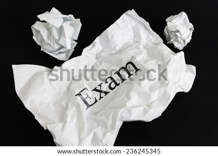 Crumpled paper sheet with word Exam isolated on black - stock photo