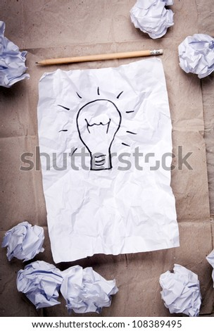 Crumpled paper with a lightbulb idea concept and crumpled paper attempts around it - stock photo