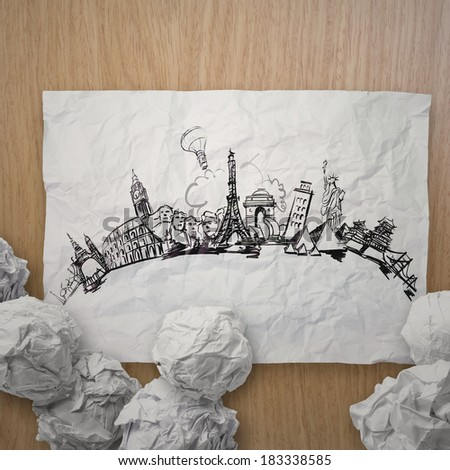 crumpled paper with hand drawn traveling around the world on wooden background as concept  - stock photo