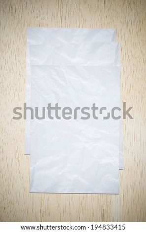 Crumpled papers on wood board.