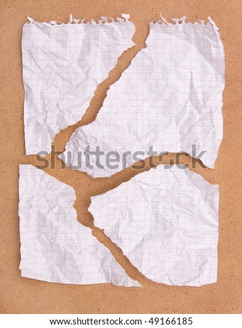 Crumpled ragged note paper isolated on brown board