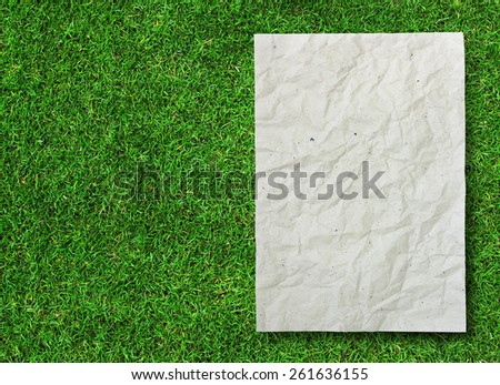 crumpled recycle paper on green grass background - stock photo