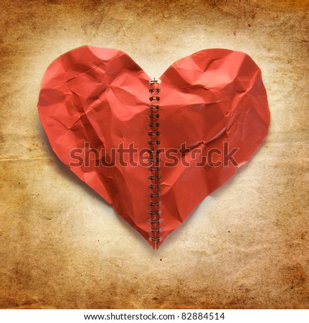 Crumpled red paper heart on vintage background. Concept. - stock photo