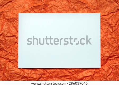 Crumpled  white paper card on orange background, place for tex - stock photo
