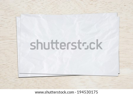 Crumpled white papers on wood board. - stock photo