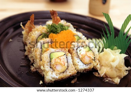 Crunch Roll sushi roll with wasabi and pickled ginger and garnished with smelt roe and chopped chives - stock photo