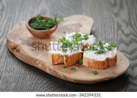 crunchy baguette slices with cream cheese and herbs on olive board - stock photo