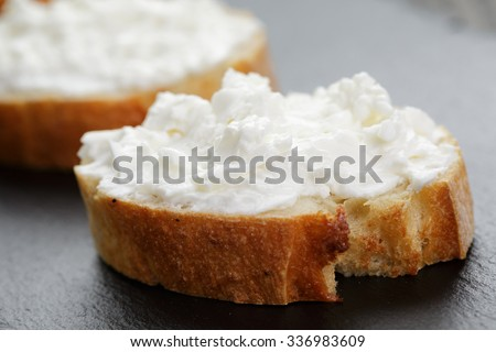 crunchy baguette slices with cream cheese on slate board - stock photo