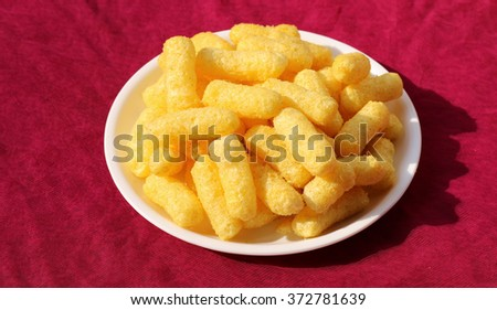 Crunchy corn puffs a tasty snacks in white pate on a red background - stock photo