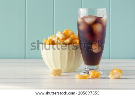 crunchy corn snacks in a bowl and a glass of soda on a white wooden table with a robin egg blue background. Vintage Style. - stock photo