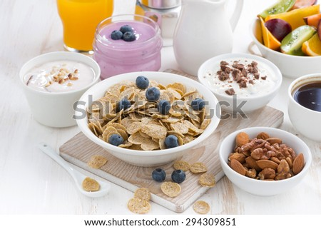crunchy flakes with blueberries and various yogurts for healthy breakfast, horizontal - stock photo