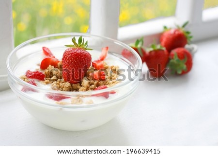 Crunchy musli (whole grain oats) served with fresh strawberries and low fat yogurt in a glass bowl - healthy breakfast on old farmhouse window sill - stock photo