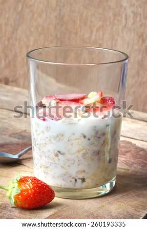 Crunchy musli (whole grain oats) served with fresh strawberries and low fat yogurt in a glass bowl - healthy breakfast. - stock photo