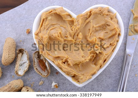 Crunchy peanut butter in white heart shape dish on dark wood vintage table.  - stock photo