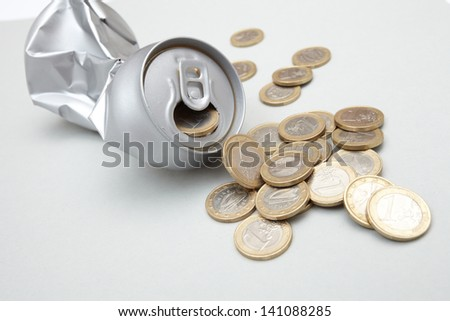 Crushed Aluminum Can with coins - stock photo