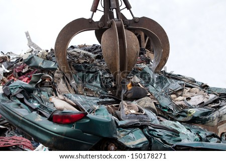 Crushed cars being picked up by a grabber