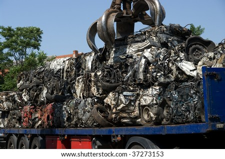 Crushed cars being put on a truck - stock photo