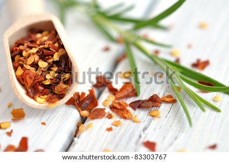 Crushed chilli pepper in a wooden scoop and fresh rosemary on an old white wooden table - stock photo