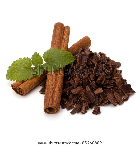 Crushed chocolate shavings pile and cinnamon sticks isolated on white background - stock photo