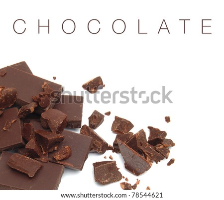 Crushed dark chocolate pieces on white background - stock photo