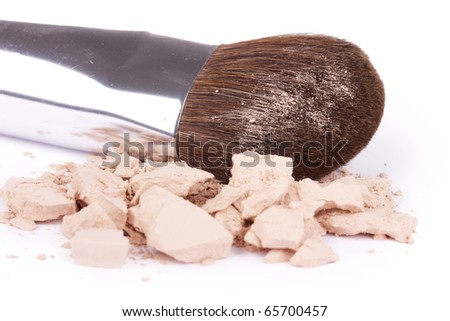 Crushed eyeshadows with professional make-up brush, closed-up on white - stock photo