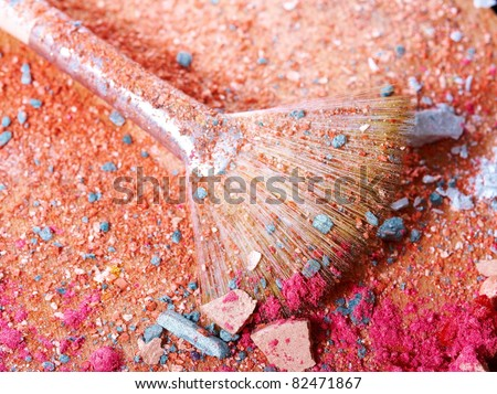 Crushed eyeshadows with professional make-up brush, closeup on wooden art palette - stock photo