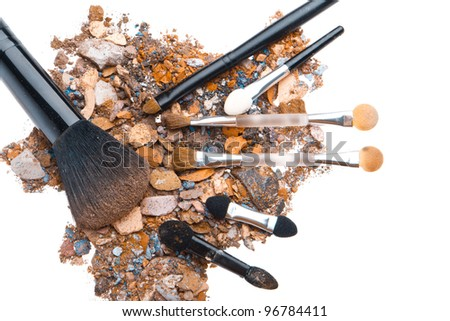 crushed eyeshadows with set of brushes isolated on white background - stock photo