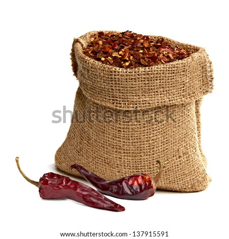 Crushed pimienta roja red pepper in sack with dried chili peppers on white background - stock photo