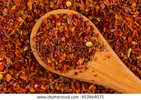 Crushed red chili pepper and wooden spoon - stock photo