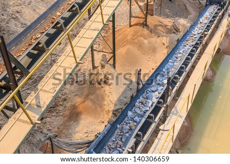 crushed rock passing conveyor belt at mining industry - stock photo