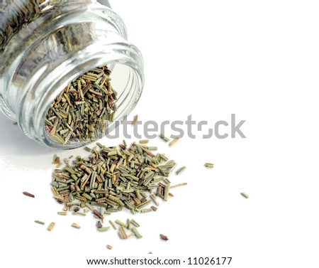crushed rosemary spice spilled on a white surface - stock photo